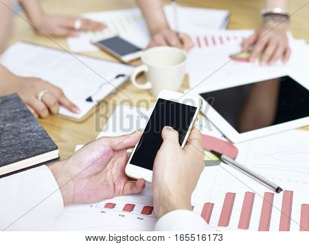 a group of young business people meeting in office analyzing sales performance and trends.