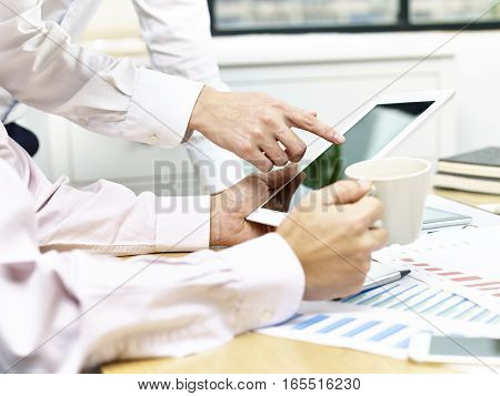 two business executives sitting at desk discussing sales performance using tablet computer.