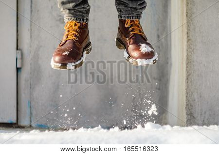 Man jump on a snowy street. Brown leather shoes in the snow.