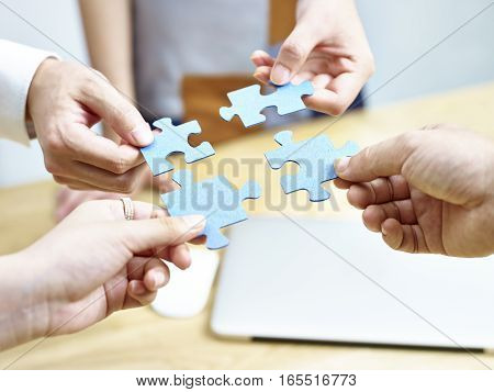 group of business people putting jigsaw pieces together