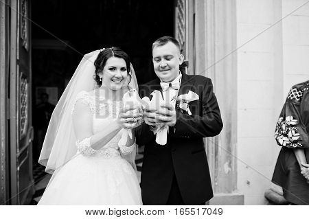Happy Smiled Wedding Couple With Doves On Hands After Wedding Registration On Church. Black And Whit