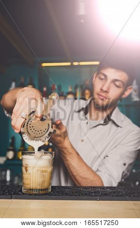 Barman's hands in bar interior making alcohol frothy cocktail. Professional bartender at work in bar pouring coconut syrup into glass. Party time in night club. Service industry occupation