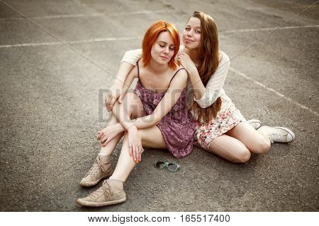 Two Teen Girls Sitting On The Playground