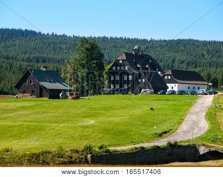 Jizerka - small idyllic mountain glassmaker village in Jizera Mountains, Northern Bohemia, Czech Republic, Europe. Sunny summer day shot with blue sky