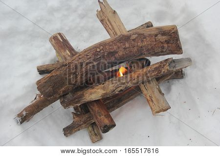 Wood stacked like a log cabin waiting for the fire to catch in the snow