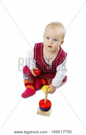 Adorable little baby girl in red dress sitting and playing with wooden toys - isolated over white background.
