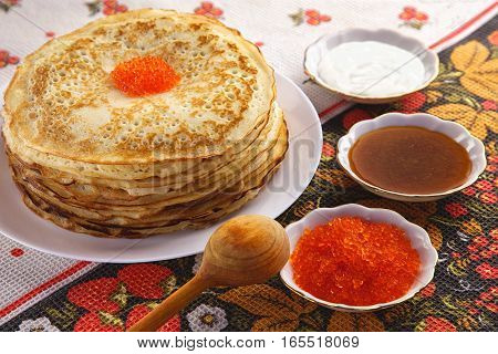 Traditional Russian pancakes with red caviar sour cream and honey