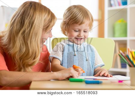 Mother and little boy of three years having fun painting at home