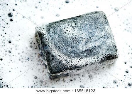 Black Coal Bar Of Soap In Foam On Dark