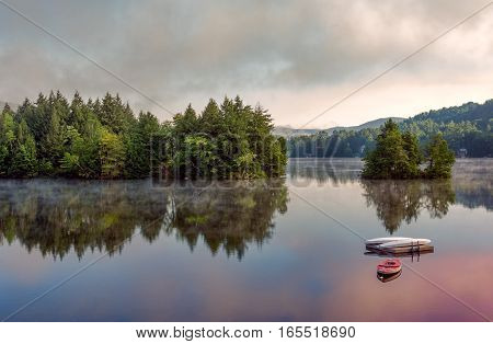 A lake in the early morning with fog on the water. A boat and dock are in the foreground.