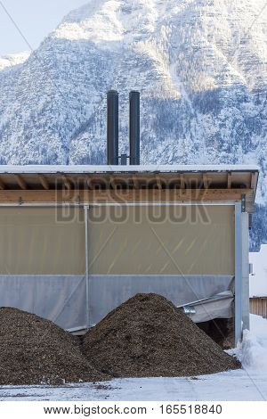 Pile of Wood Chip Biofuel in Front of Small Heating Power Plant in Mountains Ready to Produce Heat Energy