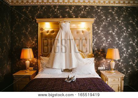 White wedding dress hanging on a bed