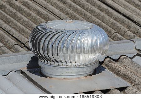 Rotating heat extractor on top of a restaurant roof.