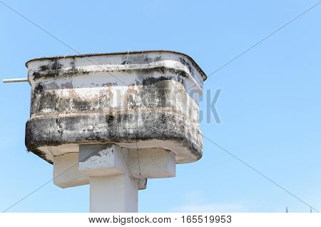 Improvised water tank. Water box of a poor house fixed with wire on a pillar.