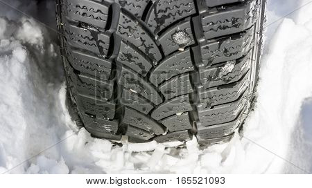 Car Tire On The Snowy Road Close Up. Winter Driving Conditions.