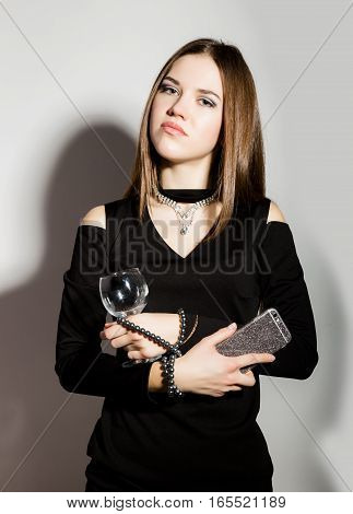 Fashion business beautiful young women in a little black dress with accessories, holding phone and empty wine glass.