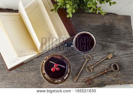 Old vintage books and cup with tea cake and keys on table on rustic wooden background