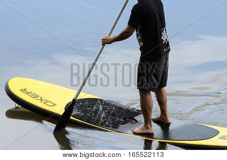 Londrina PR Brazil - December 24 2016: Man practicing Stand Up Paddle in the waters of Lake Igapó in Londrina PR Brazil.