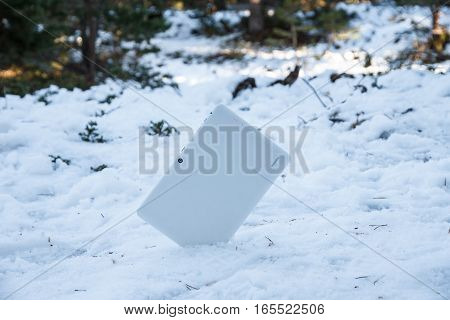 White tablet half buried in the snow in full mountain on a snowy day. Concept of technology that makes personal relationships cooler every time.