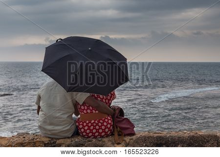 Rear View of a Indian couple sitting by sea with an umbrella looking at storm on ocean horizon.