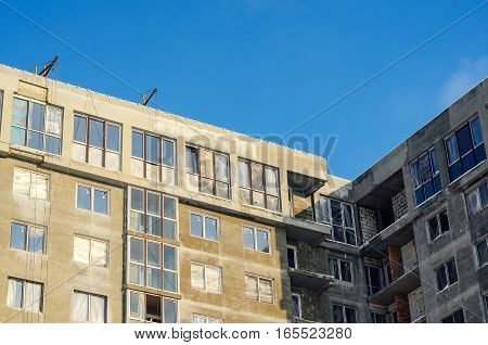 Construction site. Decorating an apartment house facade. Element of unfinished facade