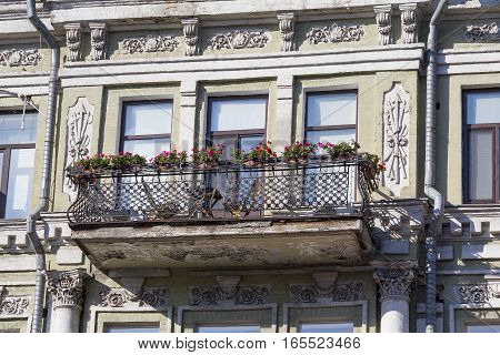 Balcony with flowers on the facade of the old building. Architecture