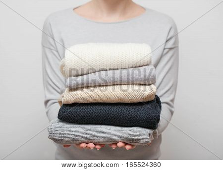 Woman holding stack of sweaters on grey background