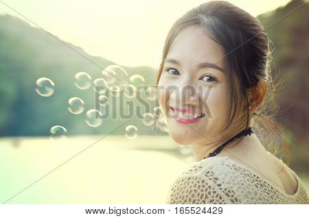 Portrait photo of Thai girl with smiley face in Pang Ung lake Mae Hong Son in the evening time with bubble in the background
