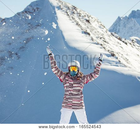 Female snowboarder wearing colorful jacket, and white pants  looking at beautiful alpine mountain landscape - snowboarding concept