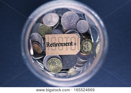 Saving Concept : Retirement label with coins in the glass