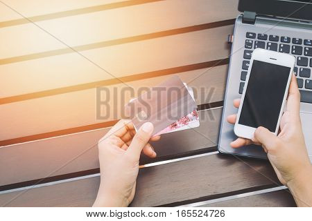 Hands holding credit card smart phone and using laptop. Online shopping concept-vintage tone and flare filtered