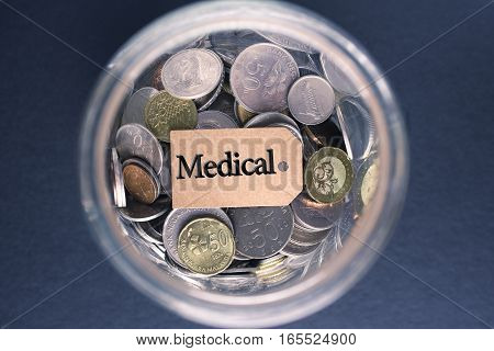 Saving Concept : Medical label with coins in the glass