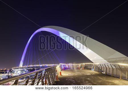 DUBAI UAE - NOV 29 2016: Blue Arch pedestrian bridge over the Dubai Water Canal illuminated at night. United Arab Emirates Middle East
