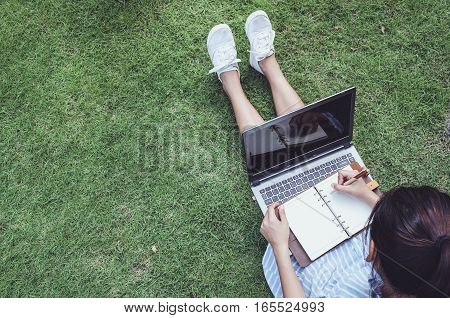 Business women using laptop and note some data on notepad with green grass background
