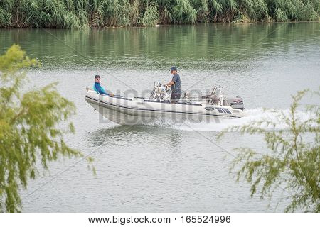 RITCHIE SOUTH AFRICA - DECEMBER 30 2016: Two unidentified people in a boat on the Riet River (reed river) at Ritchie a small town in the Northern Cape Province