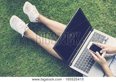 Hands using laptop and smartphone on green grass. Online shopping concept-vintage tone and flare filtered