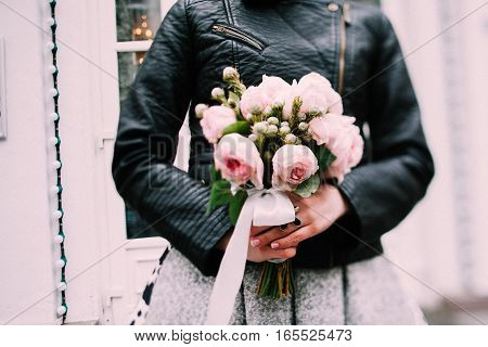 Girl holds up a bridal bouquet. Wedding bridal