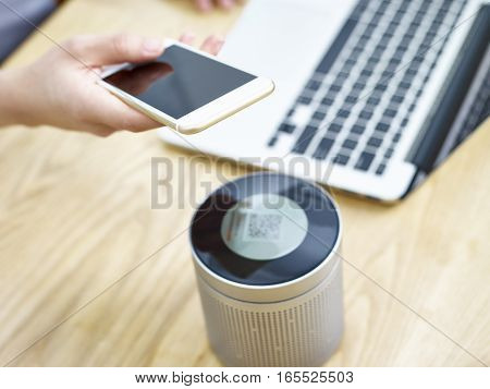 hand of a person holding cellphone playing music through a portable speaker.