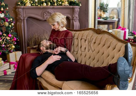 man put his head on the knees girl sitting on the sofa. Christmas tree and new year gift at home. Young family together