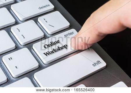 Finger on computer keyboard keys with Online Workshop word