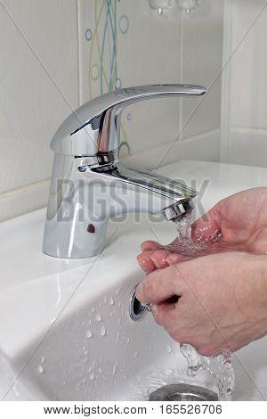 washing hands under a stream of water
