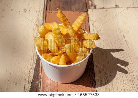 Tasty cardboard bowl of homemade French fries on wooden table background food takeaway concept.