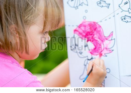 Young Girl Painting Cardboard House In the Garden