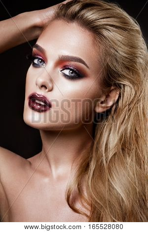 Portrait of beautiful young woman with long blonde hair and colored make-up