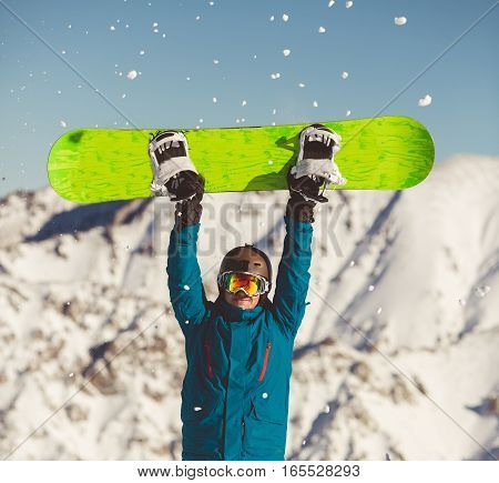 Snowboarder wearing colorful jacket, standing with snowboard in hands and looking at beautiful alpine mountain landscape - snowboarding concept