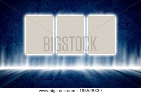 Three backlit posters in mysterious glowing interior hanging on the dark blue concrete wall. Background, template, mock up