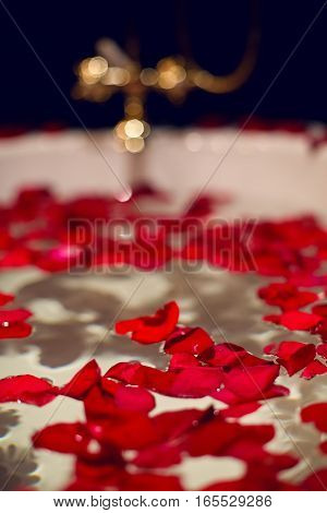 petals of red roses in a white bathroom with black tiles and gold taps