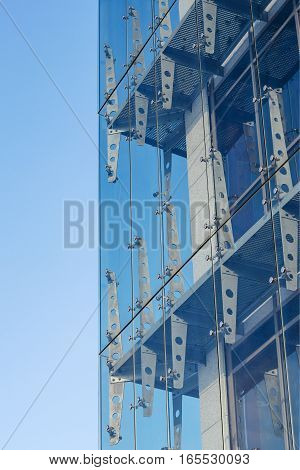 Glass curtain walls. Spider facade fixing system against the blue sky. Elements of fastening of the facade. Facade detail