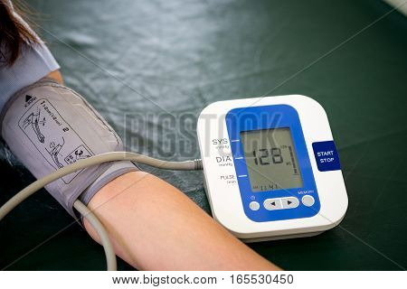 woman was checking Blood pressure by blood pressure monitor