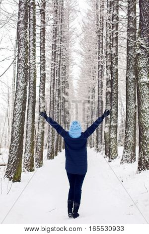 girl in the blue jacket and the cap raised on the upper arm in a grove of trees with high and snow-covered trees in winter.